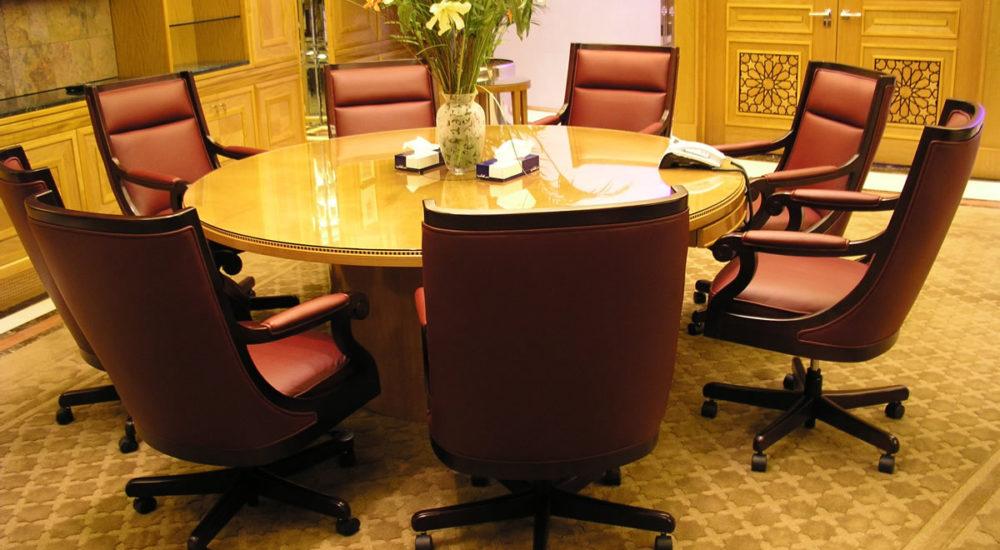 Runder Konferenztisch mit in Messing eingelegter EFG Glasplatte vor Brandschutztüre mit Furnierintarsien in Kassettenfüllungen