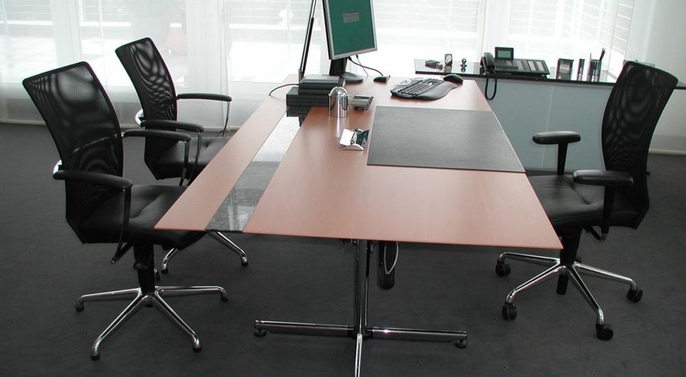 Schreibtisch in Birnbaum furniert. Die Tischplatte wird nach unten verjüngt