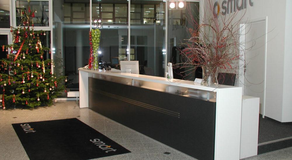 Theke mit Kabelkanal, satinierter Glaswand und Firmenlogo aus Edelstahl