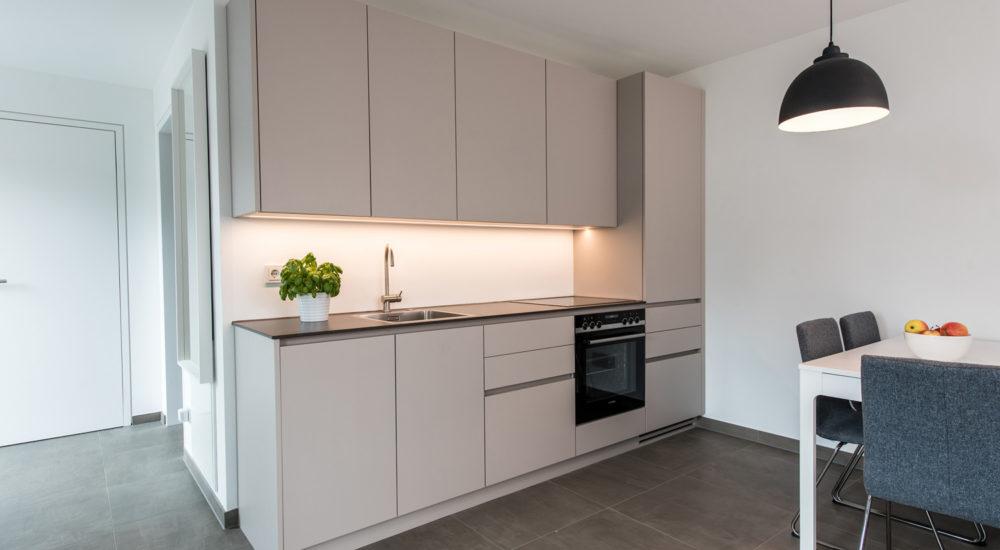 Küche mit Griffleisten und schwarzem Granit