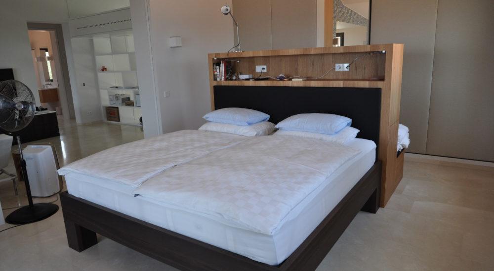 Schlafzimmern mit bepolstertem Schrank als Raumteiler zum Bad